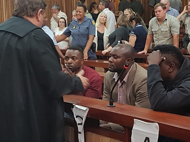 Advocate Terry Price, left, consults with the rhino poaching gang after they were found guilty in a Makhanda court. From left are Jabulani, Forget and Sikhumbuzo Ndlovu.