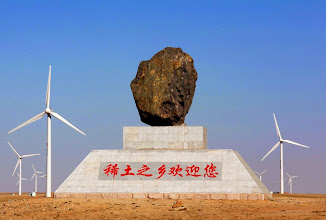 Photo: A large rock monument bearing a sign in Chinese that reads 'The Home Town of Rare Earths Welcomes You' is seen amongst a field of wind turbines near the town of Damao, located in China's Inner Mongolia Autonomous Region. China supplies 97 percent of rare earths used worldwide, and they go into magnets, bearings and high-tech components that go into computers, vehicles and, increasingly, clean energy technology such as wind turbines and hybrid cars. Picture taken October 31, 2010. TO MATCH STORY CHINA-RAREEARTHS/ REUTERS/David Gray (CHINA - Tags: ENERGY ENVIRONMENT EMPLOYMENT BUSINESS SOCIETY)