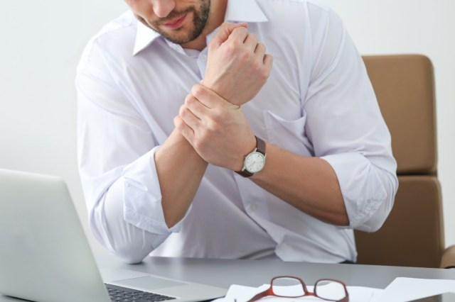 Handsome man suffering from wrist pain in office, closeup