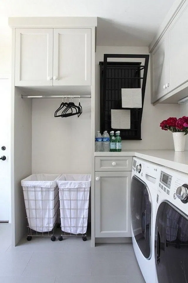 small corner laundry station with grey shaker cabinets, a wall mounted drying rack, rolling laundry bins, clothes rack and lots of counter space