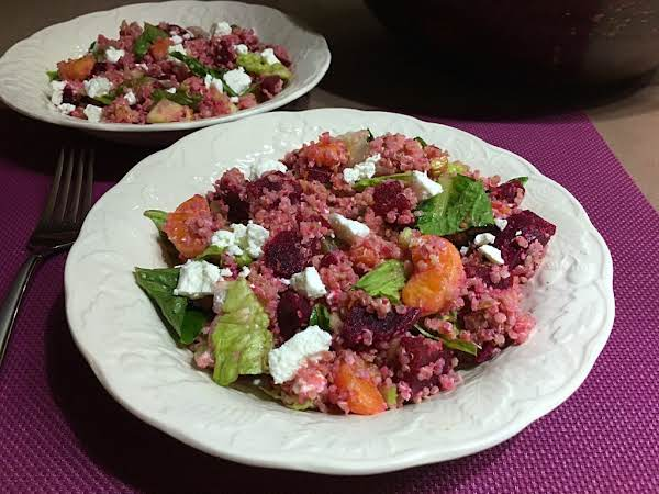 A Salad With Quinoa, Beets, Mandarin Oranges And Cheese Served In A White Bowl.