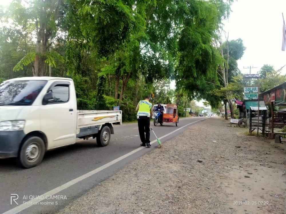 Aipda Yogi Yanto Bersihkan Pecahan Kaca Ditengah Badan Jalan Lintas Medan – Padang
