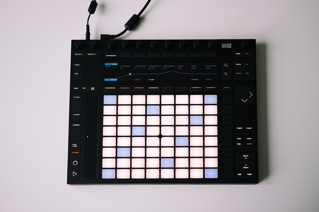 Ableton push pad, with black outer cover and white and light blue bright buttons. There are buttons with names written on them and a black charger cord plugged into the device.