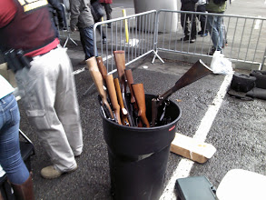 Photo: One of several trashcans with long guns after being turned in.