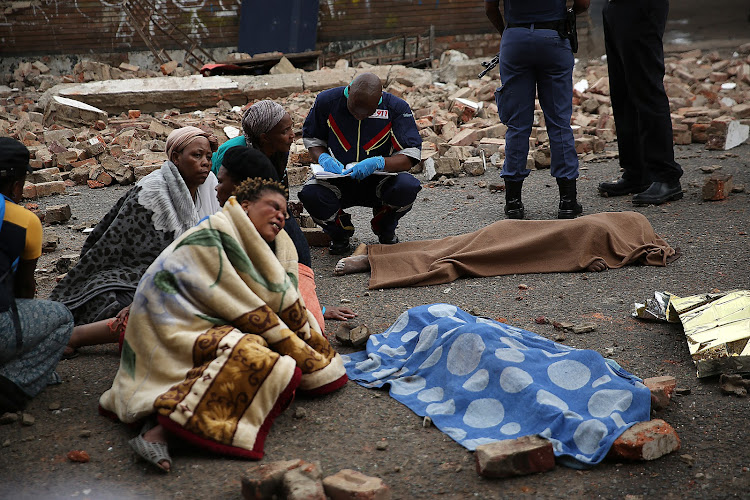 Relatives mourn the loss of young children, after a wall collapsed onto them while they were playing, in Doornfontein, Johannesburg.