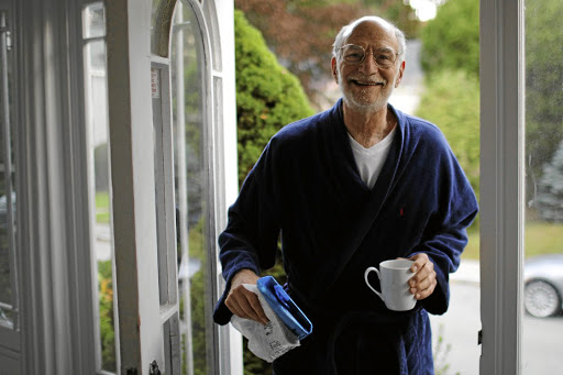 GREY EMINENCE Michael Rosbash, a professor at Brandeis University near Boston in the US, retrieves the  morning newspaper on Monday at his home in Newton, Massachusetts, after learning he is one of the 2017 Nobel prize for medicine winners Picture: Brian Snyder/Reuters
