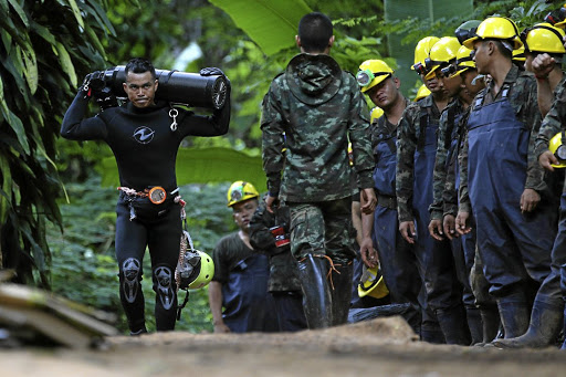 A diver carries an oxygen tank as he leaves the Tham Luang cave complex, where 12 boys and their soccer coach are trapped, in Chiang Rai, Thailand, July 6 2018. REUTERS/Athit Perawongmetha