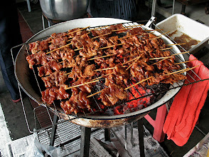 Photo: pork on sticks cooking over hot charcoal on a home-made grill, Thonglor market