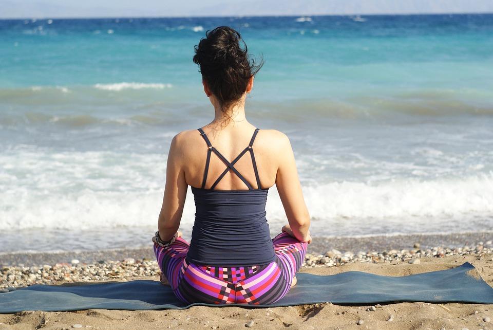 Mujer haciendo la postura del loto en la playa