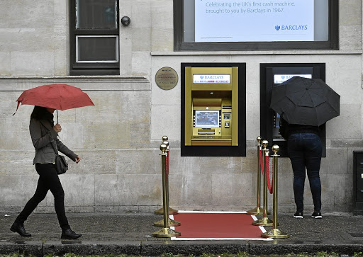 A woman uses an  ATM next to a golden one,  with red carpet and queue stanchions, that marks  the site of the first 'hole in the wall', which opened 50 years ago in London.Picture:  Reuters