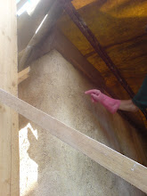 Photo: Barbara tapping on setting render to reveal areas where render has not bonded with straw (too wet on first layer, or not worked in properly...)