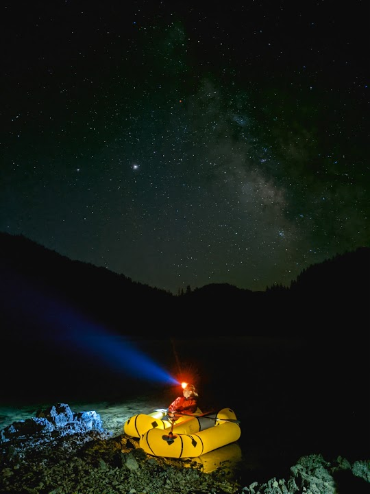 Nighttime photo of person kayaking with a clear shot of the Milky Way galaxy in background. Captured on Pixel.