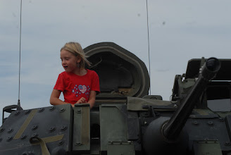 Photo: A child explores the turret of a Bradley Fighting Vehicle.