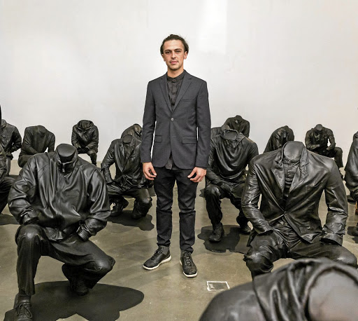 Haroon Gunn-Salie stands amid figures of headless mineworkers; the piece entitled 'Senzenina' is currently on show in London.