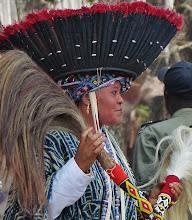 """Photo: Federhut und Tanzwedel Der """"Hut"""" besteht aus Federn - entweder von Vögeln oder Hähnen -, die in einem Bastteil verankert sind. In den Händen trägt dieTänzerin die bei rituellen Zeremonien unentbehrlichen Tanzwedel, die meist aus Pferdehaar hergestellt werden. Die Griffe sind mit bunten Perlen besetzt. Das blau-weiße Gewand weist sie als Mitglied einer königlichen Familie aus."""