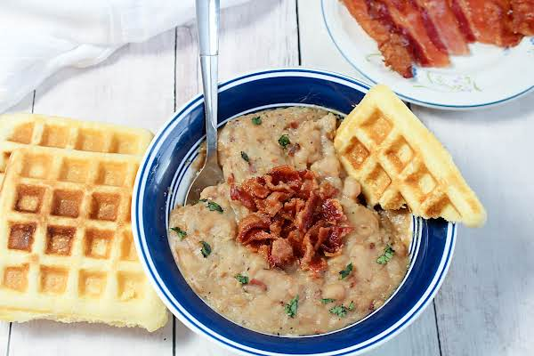 A Bowl Of Bean & Bacon Soup With Cornbread Waffles And Crumbled Bacon On Top.