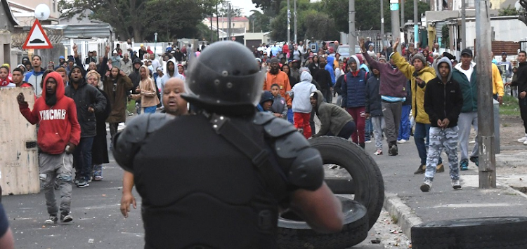 Home fires: Demonstrators attacked the police with petrol bombs, stones and golf balls in Cape Town's Parkwood on Sunday during a housing protest. Law-enforcement officials also placed a local councillor under protective custody. Picture: GALLO IMAGES/BRENTON GEACH