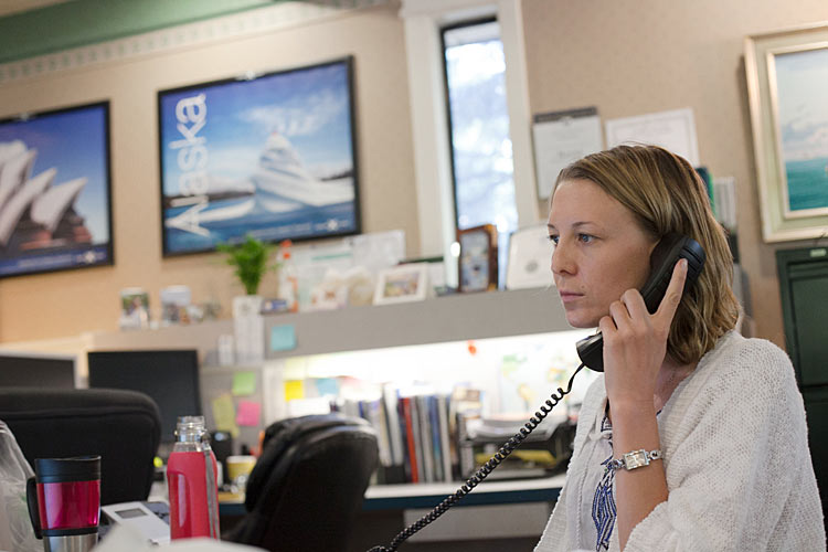 A travel agent taking a client's call. An expert travel advisor can often get you a better deal than the pricing you get directly from the cruise lines.