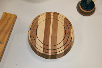Photo: This is a laminated board, made by gluing up pieces of two wood species, that has been cut on a band saw into specially-angled concentric circles.  With a simple reorganization, it will become a vessel with a parabolic banded pattern, as follows.