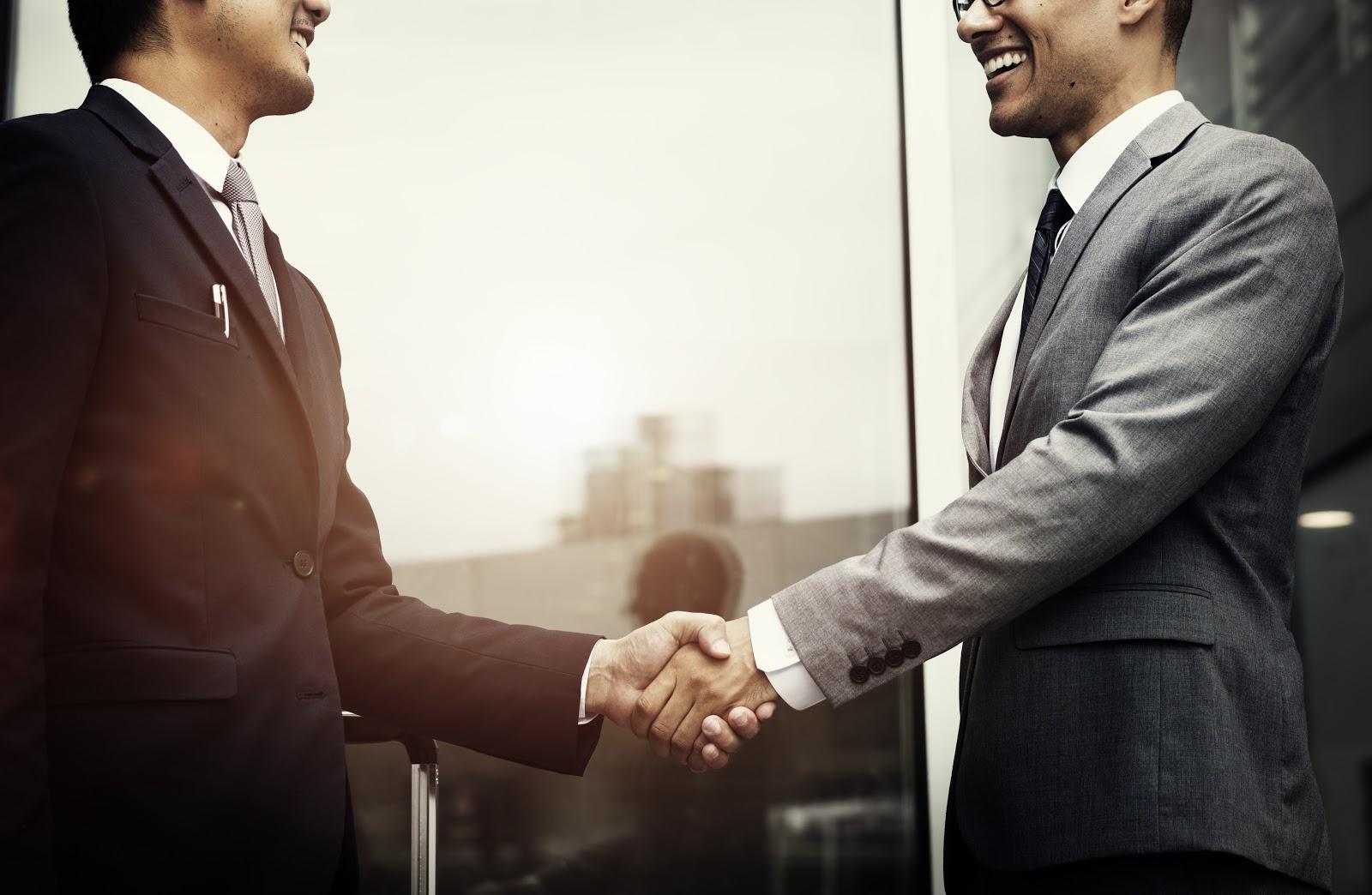 Dois colegas de trabalho vestidos com ternos apertam as mãos