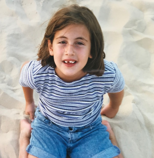 Alisa sitting on beach 8 years old with front tooth missing.