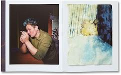 man zit te roken aan tafel; stuk boomstan staat op z'n kant tegen een muur
