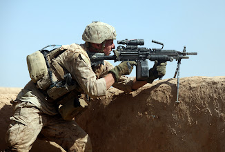 Photo: A U.S. Marine with Bravo Company, 1st Reconnaissance Battalion, 1st Marine Division (Forward), engages the enemy during a firefight in Northern Trek Nawa, Afghanistan, Aug. 15. The Marines and sailors of B Company are currently conducting counter insurgency operations in support of the International Security Assistance Force.