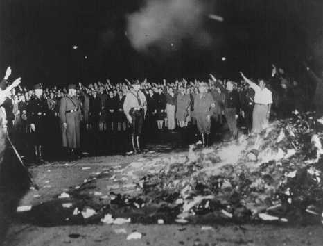 In the foreground, a massive pile of burning books. In the background, members of the German Student Union giving the Heil Hitler Salute while Nazi officers look on.