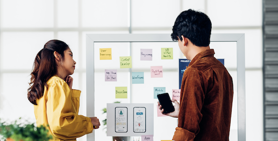 two people discussing about interface design on whiteboard
