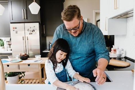 A happy father and his smiling daughter knead pizza dough onto a sheet in a kitchen as a way to help find a balance with technology.