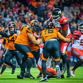 Take Down by Garry Dosa - Sports & Fitness American and Canadian football ( tackling, sports, teams, players, professionals, cfl, black, football, people, red, orange, number, white, indoors, stadium )