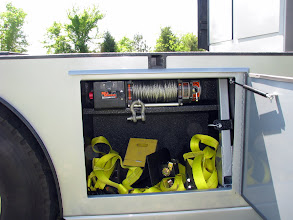 """Photo: The """"working side"""". 8K MileMarker winch. The synthetic line has not been put on yet. The winch """"arm"""" is in the bracket against the right side...it does not take up much space. Wheel nets are custom made for a smart locally. More detail on them and the chocks later. I'll put a half shelf in there to organize it better."""