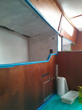 Photo: one coat of primer on pilot berth  and nav station overhead.