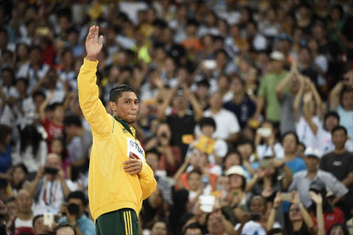 "South Africa's gold medallist Wayde van Niekerk waves on the podium during the victory ceremony for the men's 400 metres athletics event at the 2015 IAAF World Championships at the ""Bird's Nest"" National Stadium in Beijing on August 27, 2015."