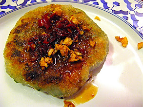 Photo: fried stuffed chive cake topped with chilli sauce and fried garlic