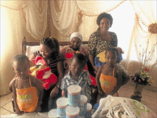 KINDNESS OF STRANGERS: Tshidi Mholo (in leopard print dress) and her niece Lesego Matabane visit Rebecca Phejane and her two sets of triplets at their home yesterday. Photo: Boitumelo Tshehle