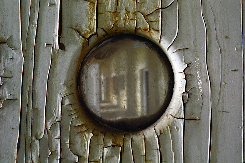 """Photo: The only remaining portion of the original complex of the Middletown State Homeopathic Hospital - later Middletown State Hospital - is the violent ward, stripped of its original roof, and suffering from heavy collapse, but still relatively intact. This 3"""" diameter window would be the only view a patient locked inside the seclusion room would have of life on the ward - and wasn't actually there for their benefit, but for that of the orderlies who would check in on the patients on a regular schedule. Sadly, since this photograph was taken, the building has suffered a large amount of vandalism and graffiti. None of these original windows remain."""