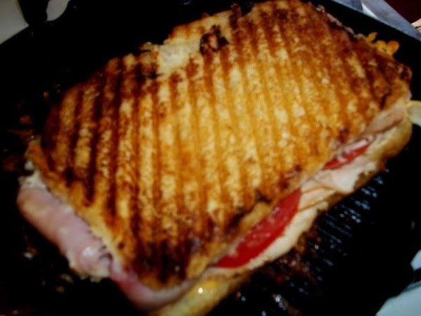 With a wide spatula, carefully flip the sandwich to the other side and weight...