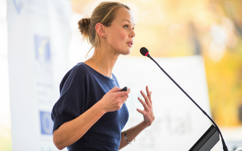 Woman speaking into a microphone at podium