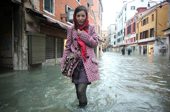 Photo: A woman walks in a flooded street during a period of seasonal high water in Venice