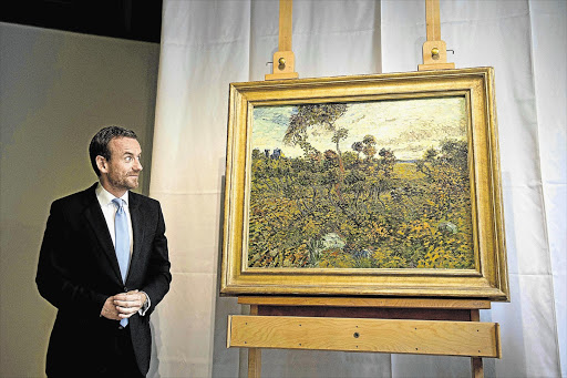 Director Axel Rueger of the Van Gogh Museum reveals a newly discovered painting by Dutch artist Vincent van Gogh in Amsterdam yesterday. The painting, 'Sunset at Montmajour', was painted in Arles in 1888