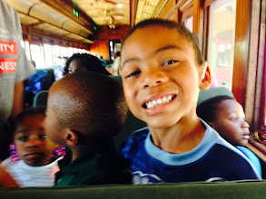 Photo: Leron Jackson, 5, happily grinning on the train ride while surrounded by other children.
