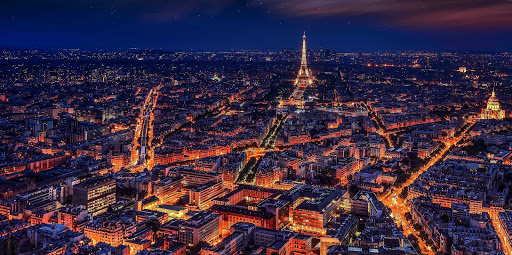 The Paris cityscape illuminated at night with the Eiffel Tower in the distance.