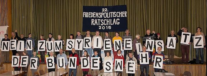Im Saal unter dem Transparent «22. Friedenspolitischer Tratschlag 2015» steht eine Menschengruppe, jeder mit einem Buchstaben und bilden die Forderung: «Nein zum Sytirneinsatz der Bundeswehr».