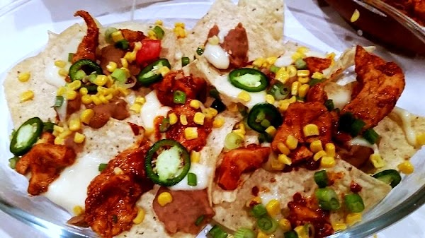 In a large casserole dish place half the tortilla chips. Dollop evenly with half...