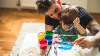 image of man helping young boy paint