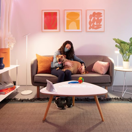 Woman wearing a mask and sitting with a dog on a couch in the Google Store experience space