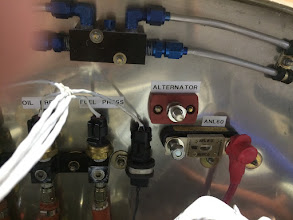 Photo: Pressure manifold to the left, oil temperature connector in the Adel clamp, and ANL60 fuse and alternator bulkhead fitting.  Need a bus bar between the ANL60 and the Blue Sea Bulkhead fitting.  Fuel Tank vent manifold to the top.