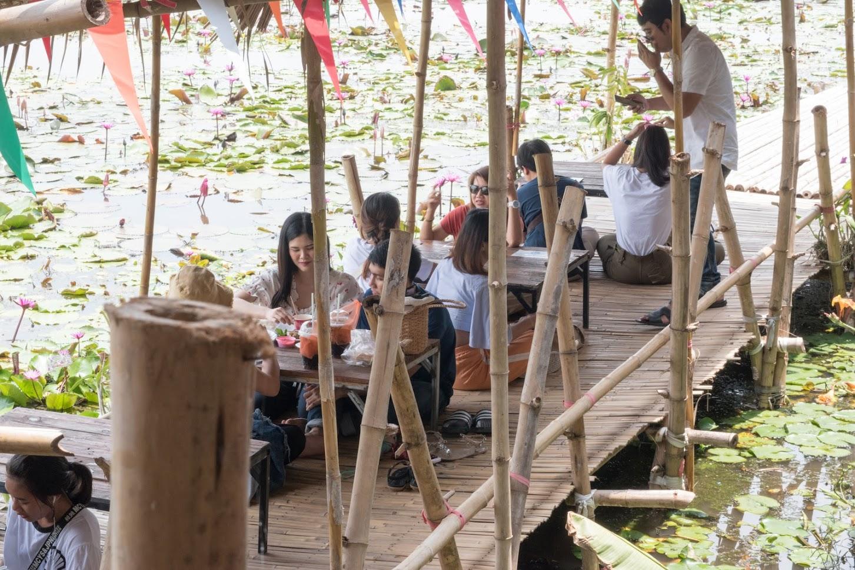 池の上にある座敷でご飯を食べる人たち