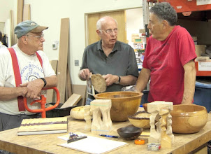 "Photo: Bob Grudberg (left) and Clif Poodry (right) discuss the green spalt ring in Bill Long's ""little tree"" sculpture, made from an unusual poplar burl, with him behind the Show Tell & Ask table."